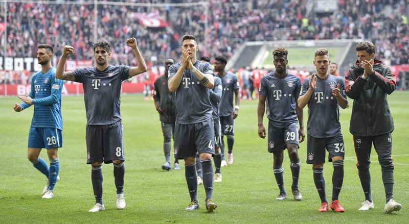 Bayern's players celebrate with supporters after winning the German Bundesliga soccer match between Fortuna Duesseldorf and Bayern Munich in Duesseldorf, Germany, Sunday April 14, 2019. (AP Photo/Martin Meissner)