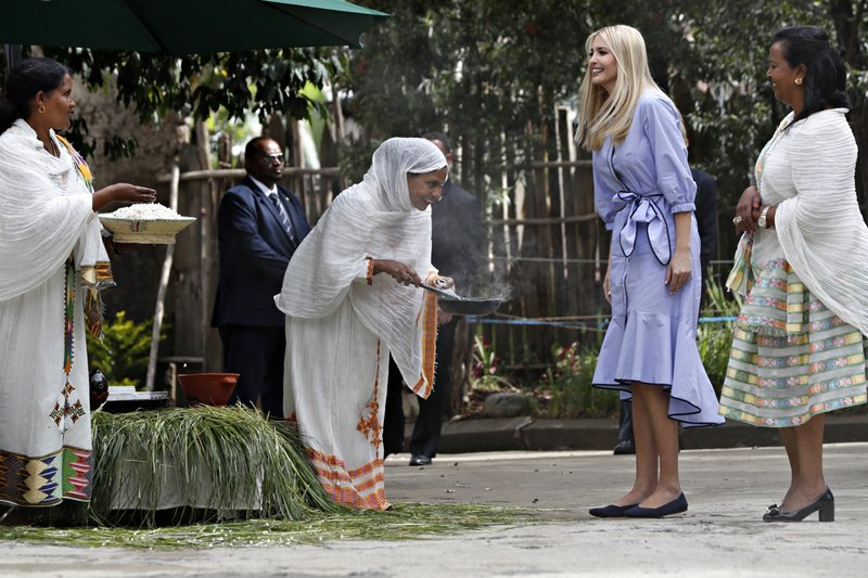 A woman bows while roasting coffee beans as another holds out a bowl of popcorn as they greet White House senior adviser Ivanka Trump, with Muya founder Sara Abera, as she arrives at the manufacturing center of textile and traditional crafts, Sunday April 14, 2019, in Addis Ababa, Ethiopia. (AP Photo/Jacquelyn Martin)