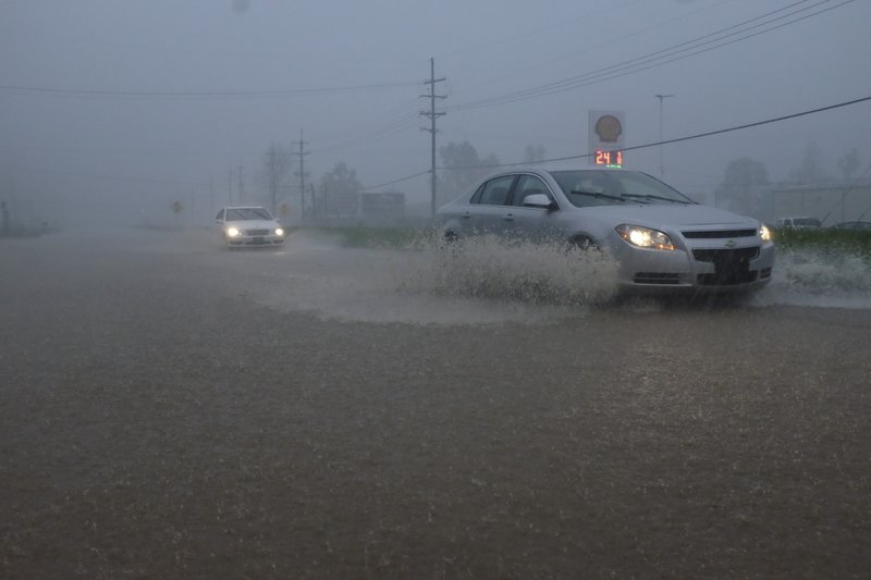 Vehicles travel through a flooded section of Highway 61 South following severe weather on Saturday, April 13, 2019 in Vicksburg, Miss. (Courtland Wells/The Vicksburg Post via AP)