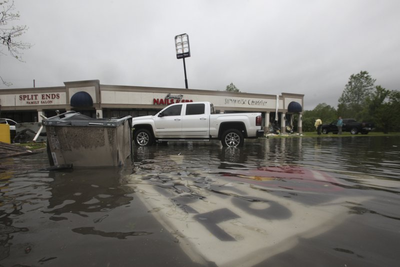 Debris is strewn in flooded water in the Pemberton Quarters strip mall following severe weather Saturday, April 13, 2019 in Vicksburg, Miss. (Courtland Wells/The Vicksburg Post via AP)