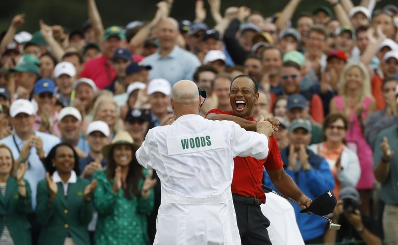 Tiger Woods reacts with his caddie Joe LaCava as he wins the Masters golf tournament Sunday, April 14, 2019, in Augusta, Ga. (AP Photo/Matt Slocum)