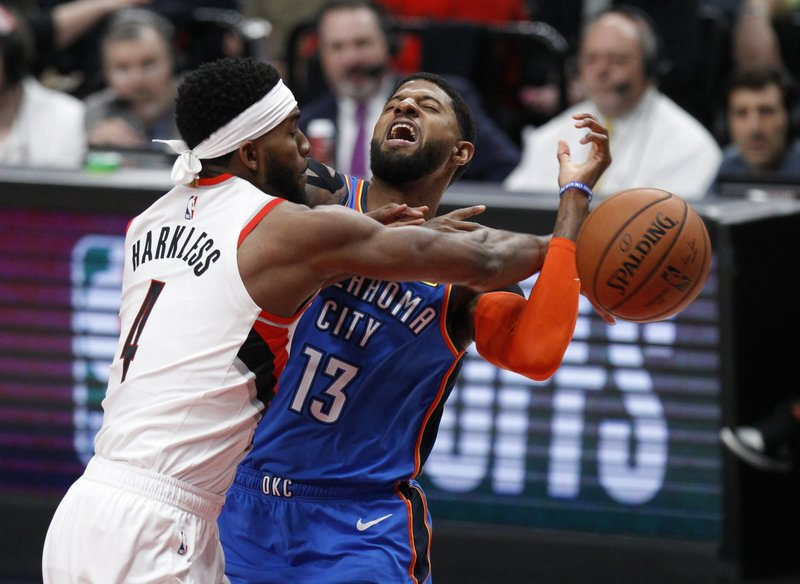 Portland Trail Blazers forward Maurice Harkless, left, knocks the ball away from Oklahoma City Thunder forward Paul George, right, during the first half of Game 1 of a first-round NBA basketball playoff series in Portland, Ore. (AP Photo/Steve Dipaola)