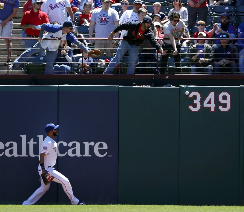 Texas Rangers right fielder Nomar Mazara watches a fans reach out for a Oakland Athletics' Khris Davis double in the first inning of a baseball game in Arlington, Texas, Sunday, April 14, 2019. (AP Photo/Tony Gutierrez)