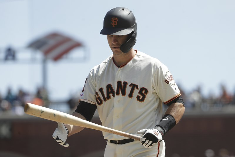 San Francisco Giants' Buster Posey walks to the dugout after striking out against the Colorado Rockies during the fourth inning of a baseball game in San Francisco, Sunday, April 14, 2019. (AP Photo/Jeff Chiu)