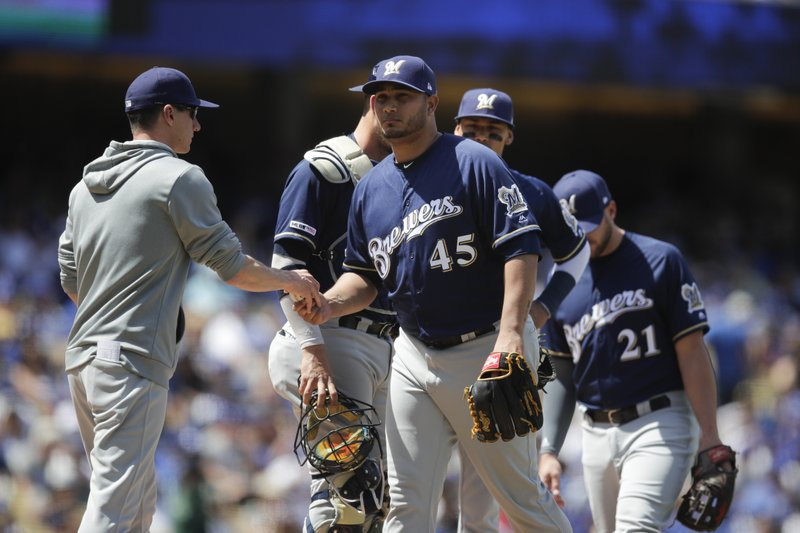 Milwaukee Brewers starting pitcher Jhoulys Chacin, center, is relieved by manager Craig Counsell during the third inning of a baseball game against the Los Angeles Dodgers, Sunday, April 14, 2019, in Los Angeles. (AP Photo/Jae C. Hong)