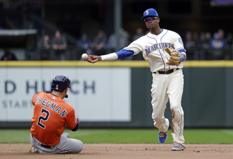 Seattle Mariners shortstop Tim Beckham, right, throws to first after forcing out Houston Astros' Alex Bregman (2) at second base in the eighth inning of a baseball game Sunday, April 14, 2019, in Seattle. (AP Photo/Elaine Thompson)