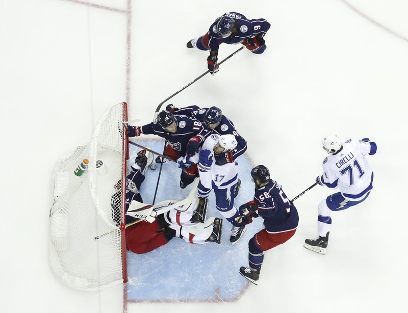Columbus Blue Jackets' Sergei Bobrovsky, left, of Russia, makes a save against the Tampa Bay Lightning as a scrum breaks out in front of the goal during the first period of Game 3 of an NHL hockey first-round playoff series Sunday, April 14, 2019, in Columbus, Ohio. (AP Photo/Jay LaPrete)