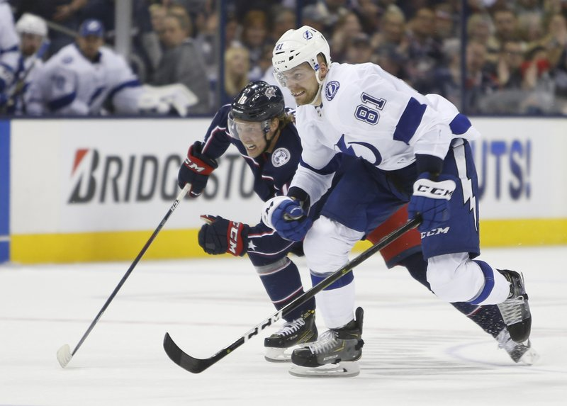 Columbus Blue Jackets' Ryan Dzingel, left, and Tampa Bay Lightning's Erik Cernak, of Slovakia, chase a loose puck during the second period of Game 3 of an NHL hockey first-round playoff series Sunday, April 14, 2019, in Columbus, Ohio. (AP Photo/Jay LaPrete)