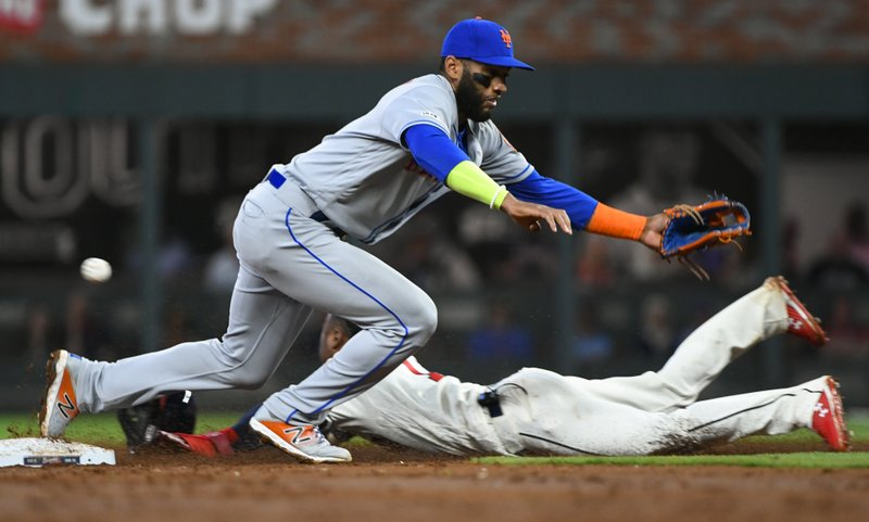 Atlanta Braves' Ozzie Albies steals second base as New York Mets shortstop Amed Rosario misses a wild throw by catcher Wilson Ramos during the third inning of a baseball game Sunday, April 14, 2019, in Atlanta. (AP Photo/John Amis)