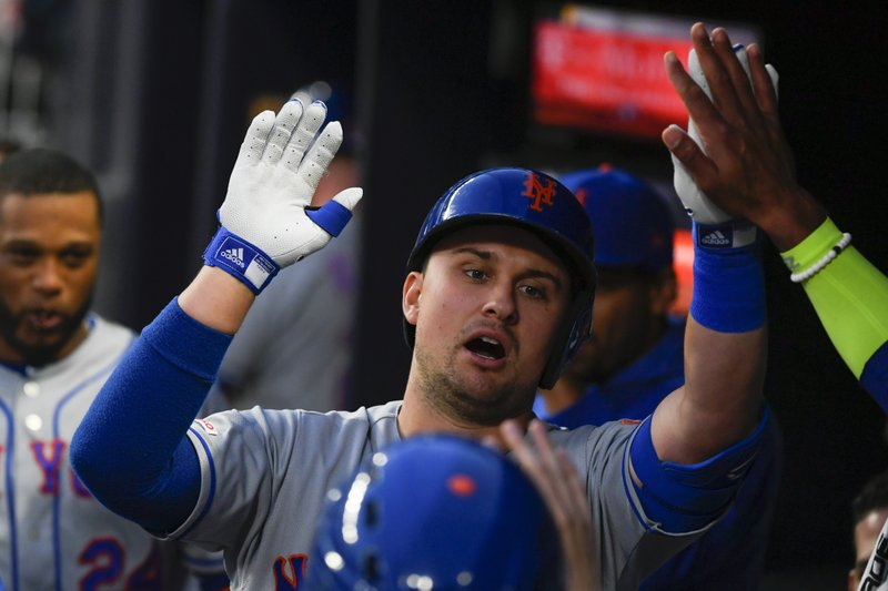 New York Mets' J.D. Davis is congratulated in the dugout after hitting a home run to center field during the second inning of a baseball game against the Atlanta Braves, Sunday, April 14, 2019, in Atlanta. (AP Photo/John Amis)