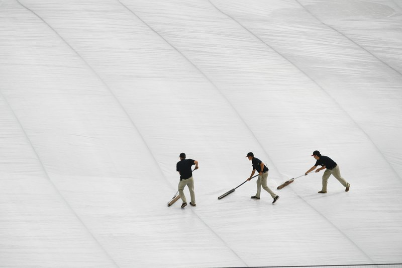 Atlanta Braves grounds crew roll water off a tarp covering the infield before a delay in the start of a baseball game against the New York Mets was announced Sunday, April 4, 2019, in Atlanta. (AP Photo/John Amis)