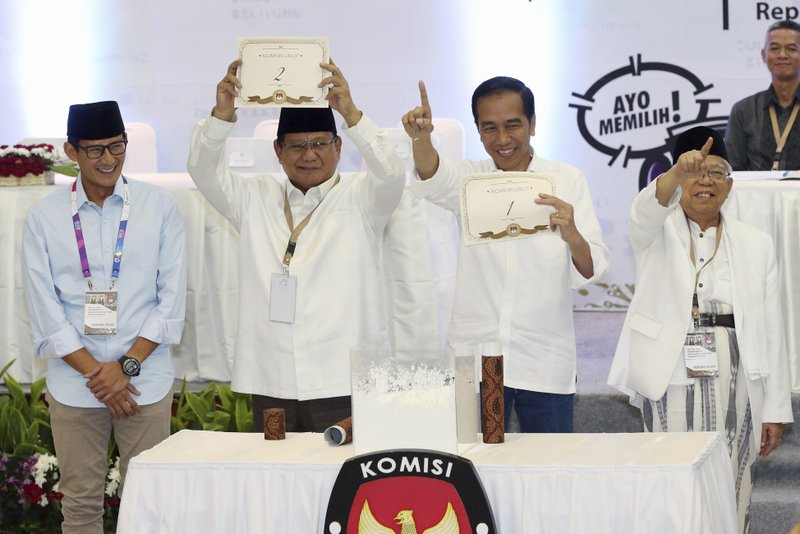 FILE - In this Sept. 21, 2018, file photo, Indonesian presidential candidates Prabowo Subianto, second from left, and his running mate Sandiaga Uno, left, Joko Widodo, second from right, and his running mate Ma'ruf Amin, show the ballot numbers that will represent them in the upcoming presidential election, during a draw at the General Election Commission office in Jakarta, Indonesia. (AP Photo/Achmad Ibrahim, File)