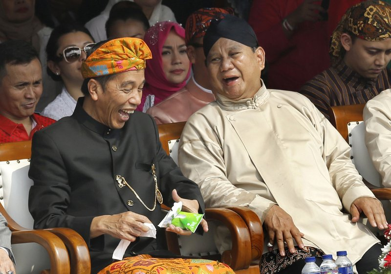 FILE - In this Sept. 23, 2018, file photo, Indonesian President Joko Widodo, left, and his contender in the upcoming election Prabowo Subianto share a light moment during a ceremony marking the kick-off of the campaign period for next year's election in Jakarta, Indonesia. (AP Photo/Tatan Syuflana, File)
