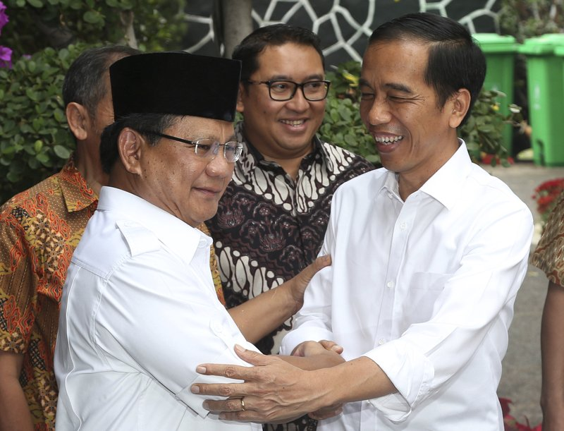 FILE - In this Oct. 17, 2014, file photo, then Indonesia's President-elect Joko Widodo, right, greets his political rival Prabowo Subianto during a meeting in Jakarta, Indonesia. (AP Photo/Tatan Syuflana, File)