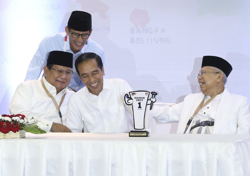 In this Sept. 21, 2018, photo, Indonesian presidential candidates, Prabowo Subianto, seated left, and Joko Widodo, second from left, share a light moment with their running mates Sandiaga Uno, top, and Ma'ruf Amin, right, during a draw for the ballot number that will represent them in the upcoming presidential election at the General Election Commission office in Jakarta, Indonesia. (AP Photo/Achmad Ibrahim, File)