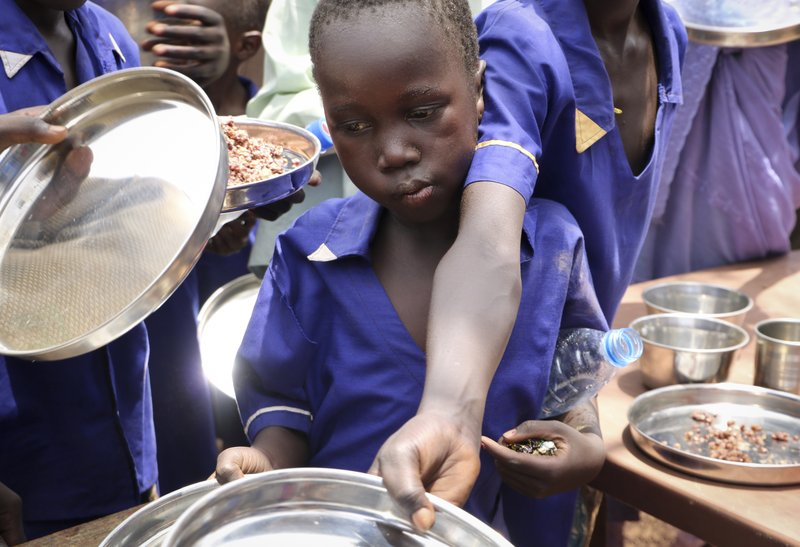 In this photo taken Tuesday, March 26, 2019, children push their plates out to receive a portion of cooked grains during a lunchtime feeding program initiative launched by UNICEF and the World Food Programme with the aim of providing daily meals to 75,000 children in Aweil, Northern Bahr el Ghazal state, in South Sudan. (AP Photo/Sam Mednick)