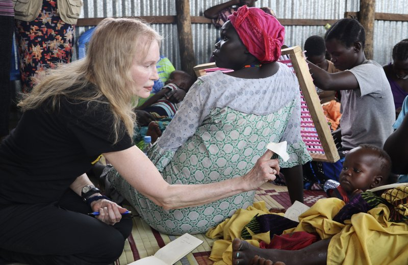 In this photo taken Tuesday, April 2, 2019, human rights activist Mia Farrow plays with a baby lying on his mother's lap while speaking to a group of women during a visit to an internally displaced person's camp in the capital Juba, South Sudan. (AP Photo/Sam Mednick)