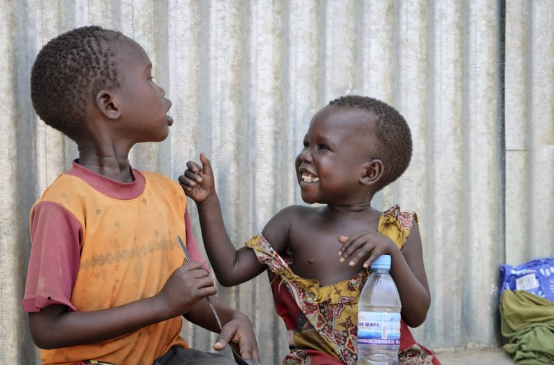 In this photo taken Tuesday, April 2, 2019, children play outside a community center at an internally displaced person's camp, during a visit by human rights activist Mia Farrow, in the capital Juba, South Sudan. (AP Photo/Sam Mednick)