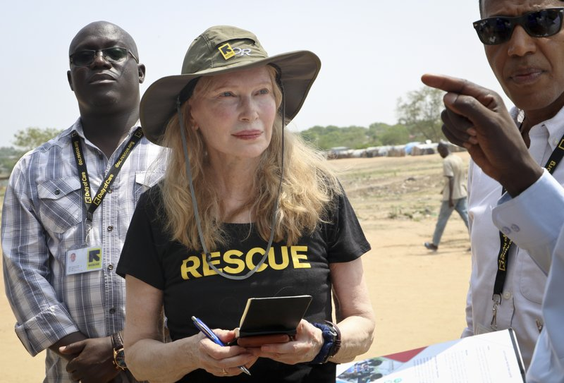 In this photo taken Tuesday, April 2, 2019, human rights activist Mia Farrow takes notes while speaking with staff from the International Rescue Committee while visiting an internally displaced person's camp in the capital Juba, South Sudan. (AP Photo/Sam Mednick)