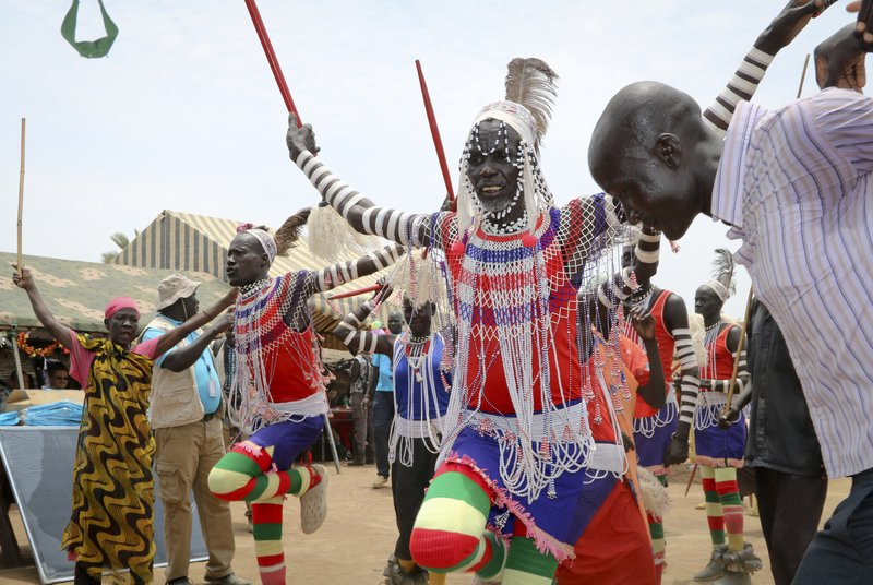 In this photo taken Tuesday, March 26, 2019, South Sudanese perform a traditional dance as they welcome donors who were launching a new joint education in emergencies initiative with the aim of providing daily meals to 75,000 children, in Aweil, Northern Bahr el Ghazal state, in South Sudan. (AP Photo/Sam Mednick)