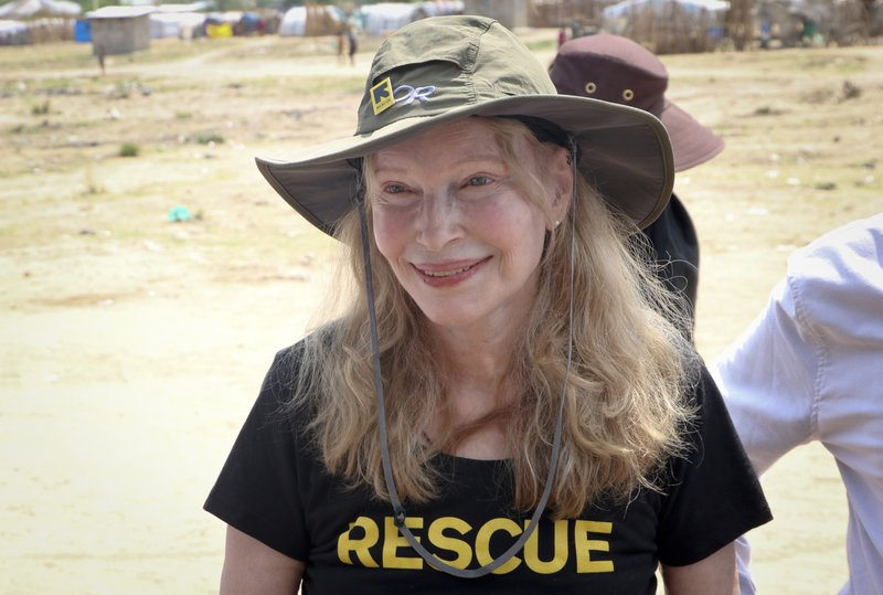 In this photo taken Tuesday, April 2, 2019, human rights activist Mia Farrow smiles while interacting with women and children in an internally displaced person's camp in the capital Juba, South Sudan. (AP Photo/Sam Mednick)