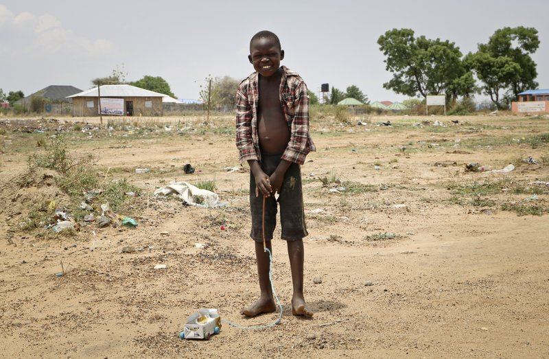 In this photo taken Tuesday, April 2, 2019, a young boy plays with a homemade toy car made from a juice carton at an internally displaced person's camp, during a visit by human rights activist Mia Farrow, in the capital Juba, South Sudan. (AP Photo/Sam Mednick)