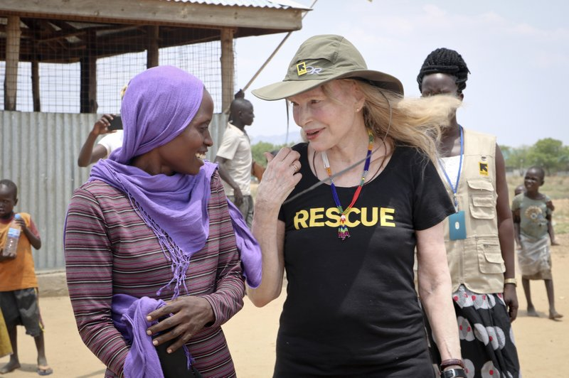 In this photo taken Tuesday, April 2, 2019, human rights activist Mia Farrow laughs with staff from the International Rescue Committee while visiting an internally displaced person's camp in the capital Juba, South Sudan. (AP Photo/Sam Mednick)