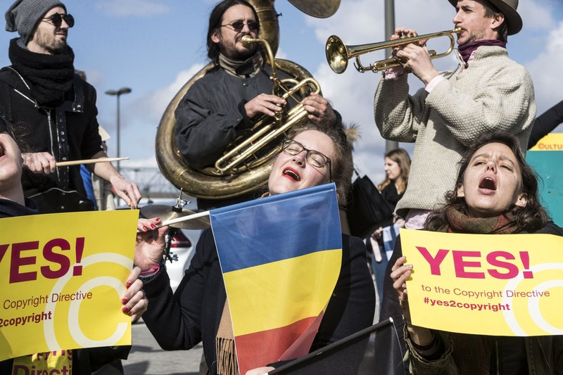 FILE - In this Tuesday March 26, 2019 file photo, people gather at the front of the European Parliament building in Strasbourg, France, to show their support for the copyright bill. (AP Photo/Jean-Francois Badias, File)