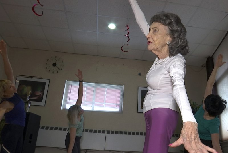 In this April 5, 2019, image made from a video, 100-year-old Tao Porchon-Lynch teaches a yoga class in Hartsdale, N. (AP Photo/Ted Shaffrey)