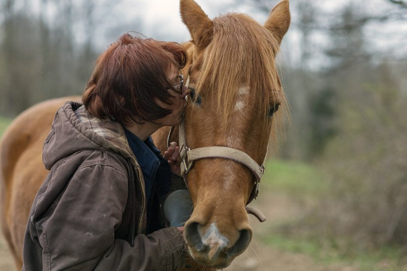 In this Friday, April 5, 2019, photo, Kelly Povroznik kisses her horse Rambling Jack goodbye after having tended to him and her other horse Blackjack at their pasture outside of Clarksburg, W. (AP Photo/Craig Hudson)
