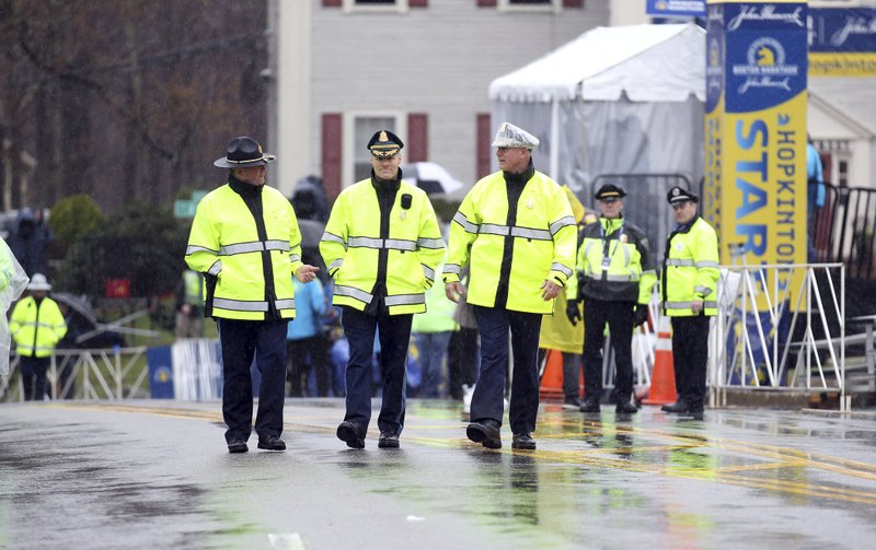 Massachusetts State Police walk the starting area of the 123rd Boston Marathon on Monday, April 15, 2019, in Hopkinton, Mass. (AP Photo/Stew Milne)