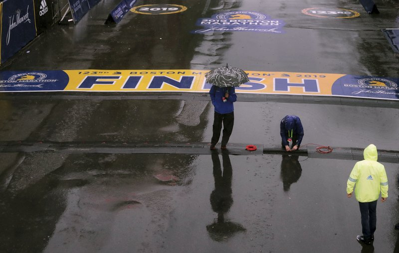 Final preparations are made in the rain at the finish line for the 123rd Boston Marathon on Monday, April 15, 2019, in Boston. (AP Photo/Charles Krupa)