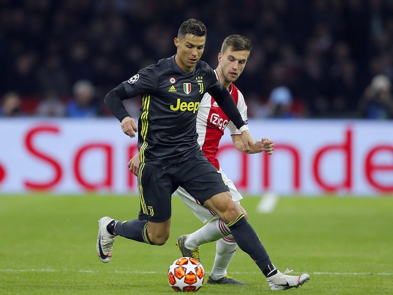 FILE - In this Wednesday, April 10, 2019 file photo, Juventus forward Cristiano Ronaldo, front, duels for the ball with Ajax's Joel Veltman during the Champions League quarterfinal, first leg, soccer match between Ajax and Juventus at the Johan Cruyff ArenA in Amsterdam, Netherlands. (AP Photo/Peter Dejong, File