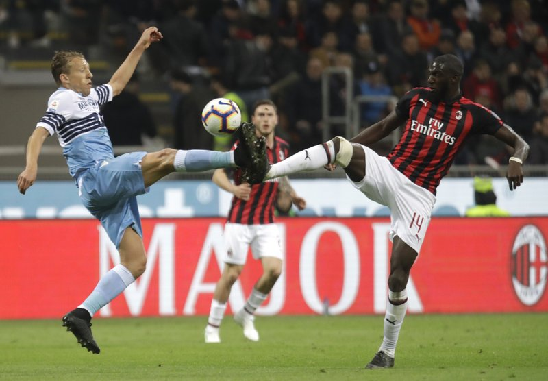 Lazio's Lucas Leiva, left, and AC Milan's Tiemoue Bakayoko challenge for the ball during the Serie A soccer match between AC Milan and Lazio, at the San Siro stadium in Milan, Italy, Saturday, April 13, 2019. (AP Photo/Luca Bruno)