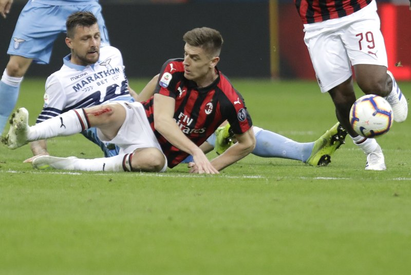 Lazio's Francesco Acerbi, left, AC Milan's Krzysztof Piatek, centre, and AC Milan's Franck Kessie challenge for the ball during the Serie A soccer match between AC Milan and Lazio, at the San Siro stadium in Milan, Italy, Saturday, April 13, 2019. (AP Photo/Luca Bruno)