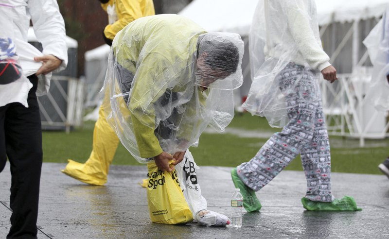 Dustin Martin, of Albuquerque, New Mexico tightens bags around his feet prior to the start of the123rd Boston Marathon on Monday, April 15, 2019, in Hopkinton, Mass. (AP Photo/Stew Milne)