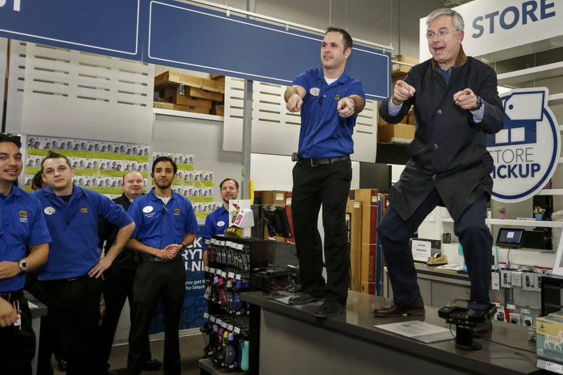 FILE - In this Nov. 26, 2015, file photo, Best Buy CEO Hubert Joly, right, leads a cheer for employees with store manager Brian Maciej before the store opens on Thanksgiving, in Minnetonka, Minn. (AP Photo/Bruce Kluckhohn, File)