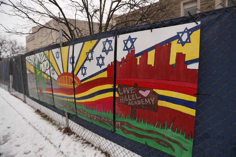 FILE--This file photo from Feb. 11, 2019 shows artwork on a fence around the Tree of Life Synagogue in Pittsburgh where 11 people were killed and seven others injured during an attack on in October of 2018. (AP Photo/Keith Srakocic, File)
