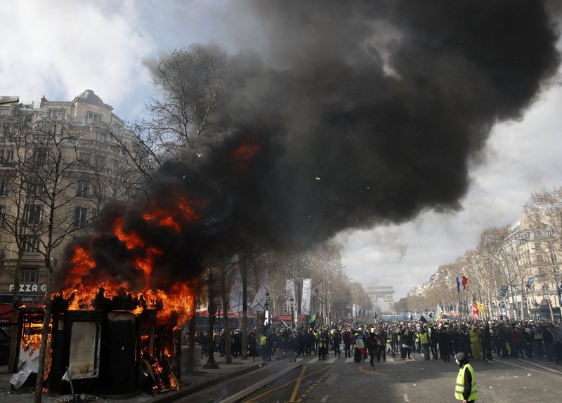FILE - In this March 16, 2019 file photo, a news stand burns during a yellow vests demonstration on the Champs Elysees avenue in Paris. (AP Photo/Christophe Ena, File)