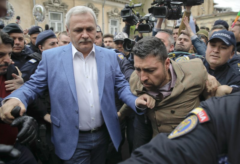 Liviu Dragnea, left, the leader of Romania's ruling Social Democratic party, arrives escorted by police officers for court hearing in a trial in Bucharest, Romania, Monday, April 15, 2019. (AP Photo/Vadim Ghirda)