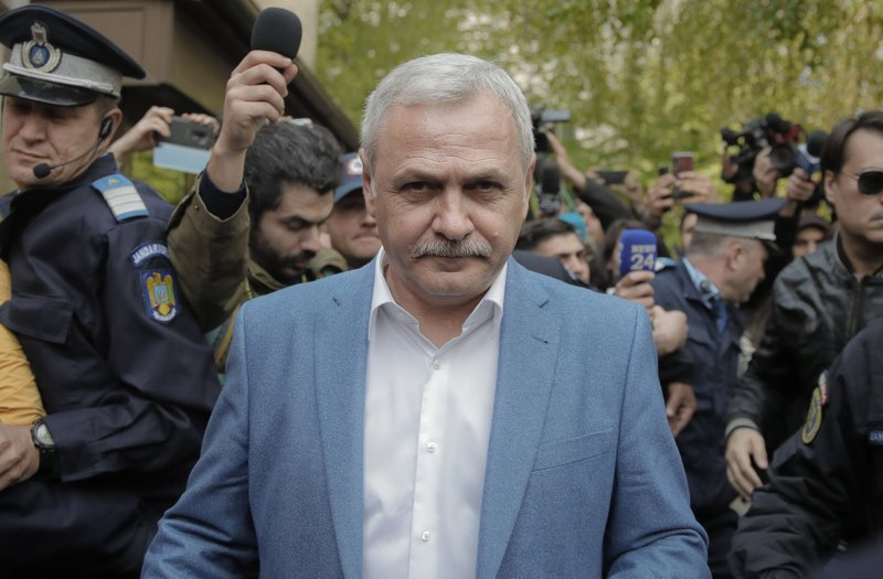 Liviu Dragnea, the leader of Romania's ruling Social Democratic party, leaves escorted by police officers after a court hearing in Bucharest, Romania, Monday, April 15, 2019. (AP Photo/Vadim Ghirda)