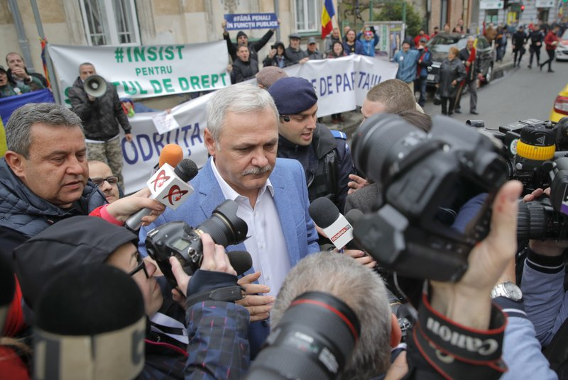 Liviu Dragnea, the leader of Romania's ruling Social Democratic party, center, arrives escorted by police officers for a court hearing in Bucharest, Romania Monday, April 15, 2019 as opponents of his party chant slogans and hold banners that translate