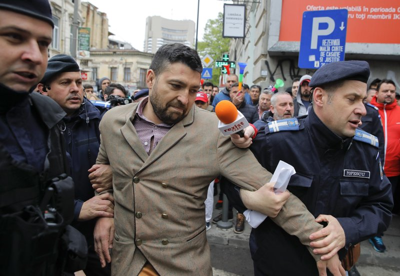 Gendarmes drag a supporter of Liviu Dragnea as brief scuffles erupted before his court hearing in Bucharest, Romania, Monday, April 15, 2019. (AP Photo/Vadim Ghirda)