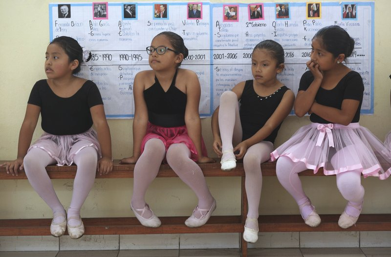 In this April 2, 2019 photo, ballet students wait for the start of their lesson at a public school in the Chorrillos neighborhood, a poor part of Lima, Peru. (AP Photo/Martin Mejia)