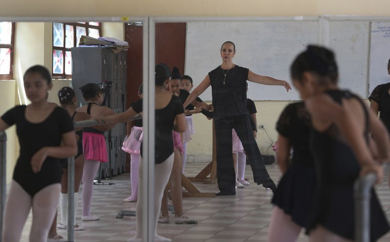 In this April 2, 2019 photo, Maria del Carmen Silva, a former professional dancer, instructs a group of young dancers in a studio at a public school in the Chorrillos neighborhood, a poor part of Lima, Peru. (AP Photo/Martin Mejia)