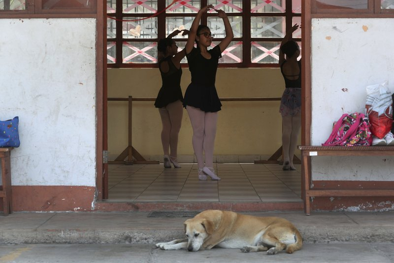 In this April 2, 2019 photo, young ballet dancers practice their technique in a studio at a public school in the Chorrillos neighborhood, a poor part of Lima, Peru. (AP Photo/Martin Mejia)