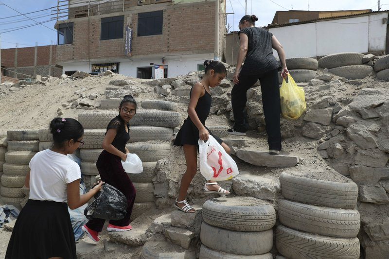 In this April 4, 2019 photo, Maria del Carmen Silva, a former professional dancer, and her ballet students, search and collect recycling plastic bottles for money, in the Chorrillos neighborhood, a poor part of Lima, Peru. (AP Photo/Martin Mejia)