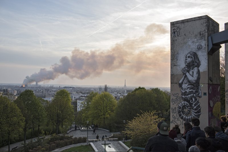 People watch Notre Dame cathedral burning in Paris, Monday, April 15, 2019. Massive plumes of yellow brown smoke is filling the air above Notre Dame Cathedral and ash is falling on tourists and others around the island that marks the center of Paris. (AP Photo/Rafael Yaghobzadeh)