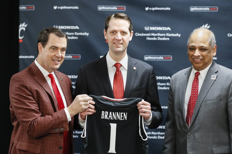 John Brannen, center, poses for a picture with athletic director Michael Robert Bohn, left, and university president Neville Pinto, right, during a news conference to formally announce Brannen's hiring as Cincinnati's men's basketball coach after leading Northern Kentucky to two NCAA Tournament appearances in the last three years, Monday, April 15, 2019, in Cincinnati. (AP Photo/John Minchillo)