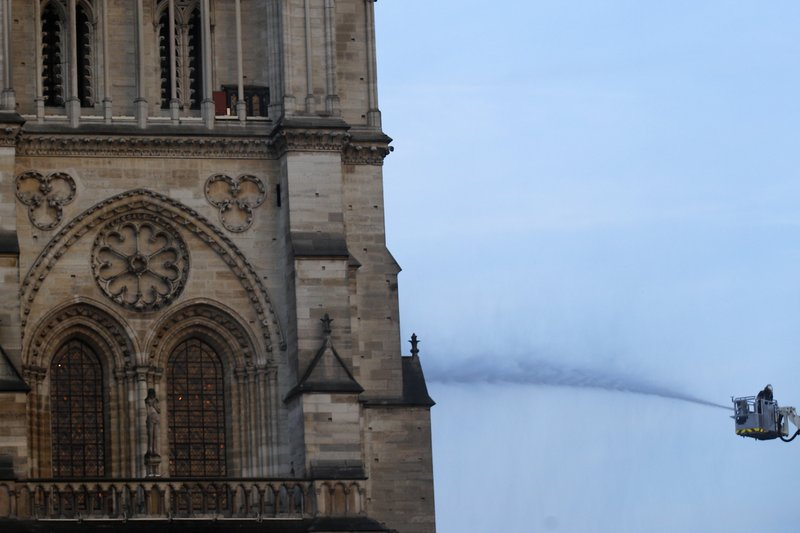 A fire fighter tackles the blaze as flames and smoke rise while Notre Dame cathedral is burning in Paris, Monday, April 15, 2019. (AP Photo/Francois Mori)